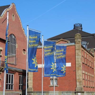 Blaue Fahnen vor dem roten Backsteingebäude des Binnenschifffahrtsmuseum Duisburg