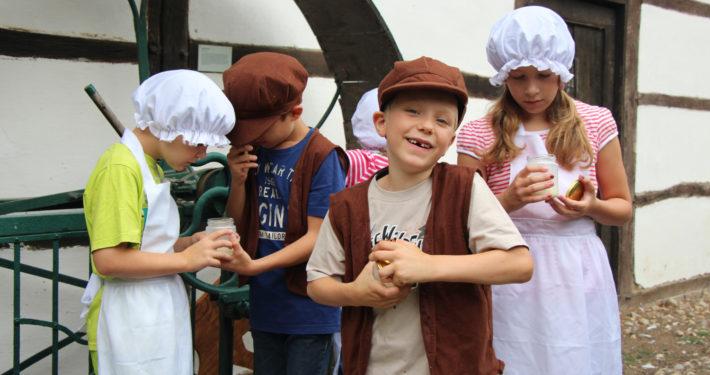 Kinder mit selbstgemachter Butter im Freilichtmuseum in Grefrath