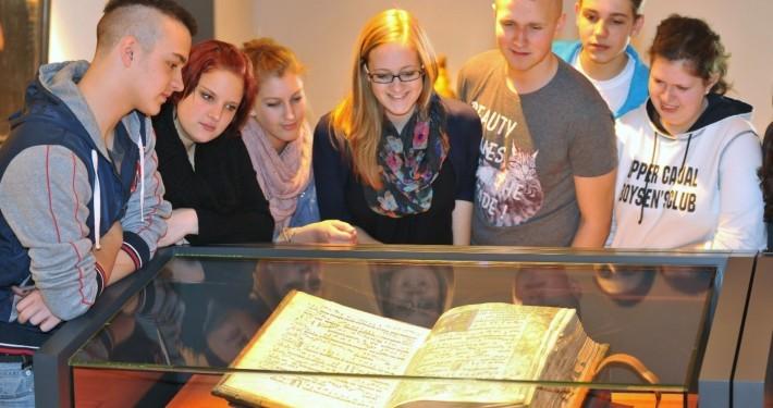 Eine Schülergruppe beschaut ein mittelalterliches Buch im Stiftsmuseum Xanten