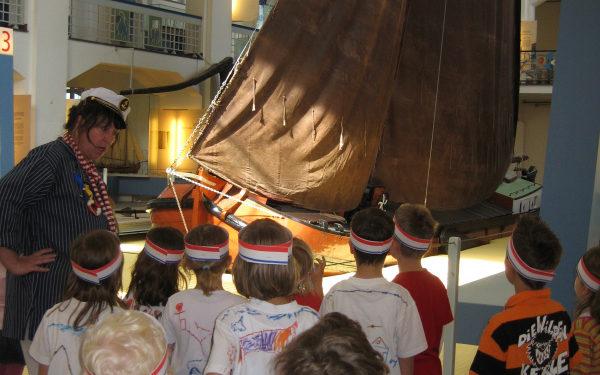 Kinder stehen vor einem Schiff mit Mast im Binnenschifffahrtsmuseum Duisburg