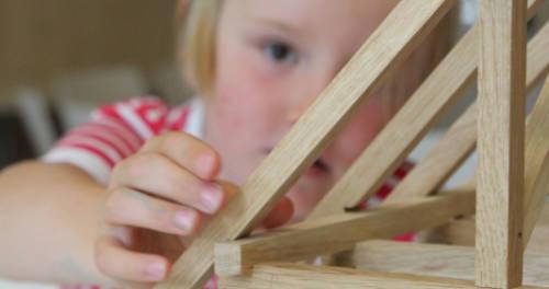Ein Mädchen baut ein kleines Fachwerkhausmodell im Freilichtmuseum in Grefrath
