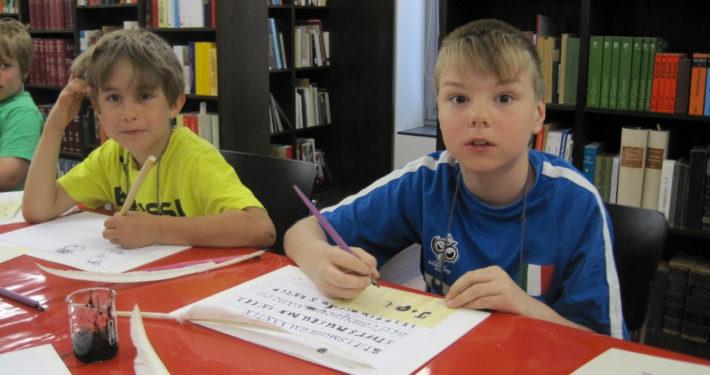 Zwei Jungen üben die mittelalterliche Schrift im Stiftsmuseum Xanten