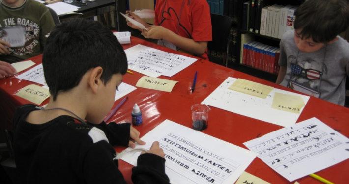 Eine Schülergruppe übt die mittelalterliche Schrift im Stiftsmuseum Xanten