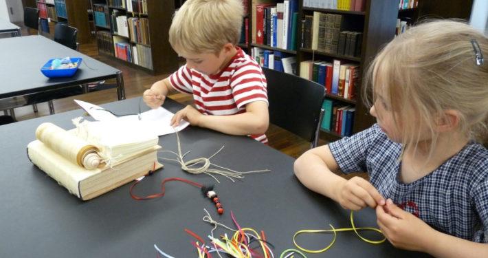 Zwei Kinder beim Bücher binden im Stiftsmuseum Xanten