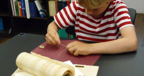 Ein Junge bindet ein Buch mit einem Faden im Stiftsmuseum Xanten