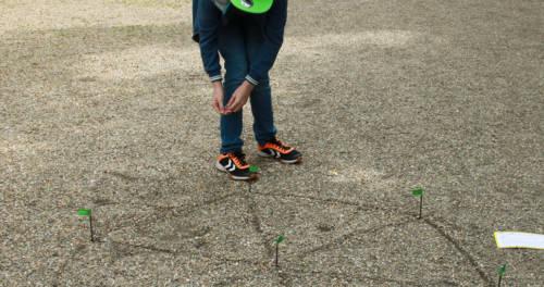 Kind zeichnet im Kies ein Pentagram